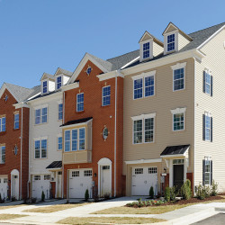 row of three story townhomes – brick & wood paneling exterior