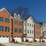 row of similar colonial three story townhomes with two car garage & brick exterior walls