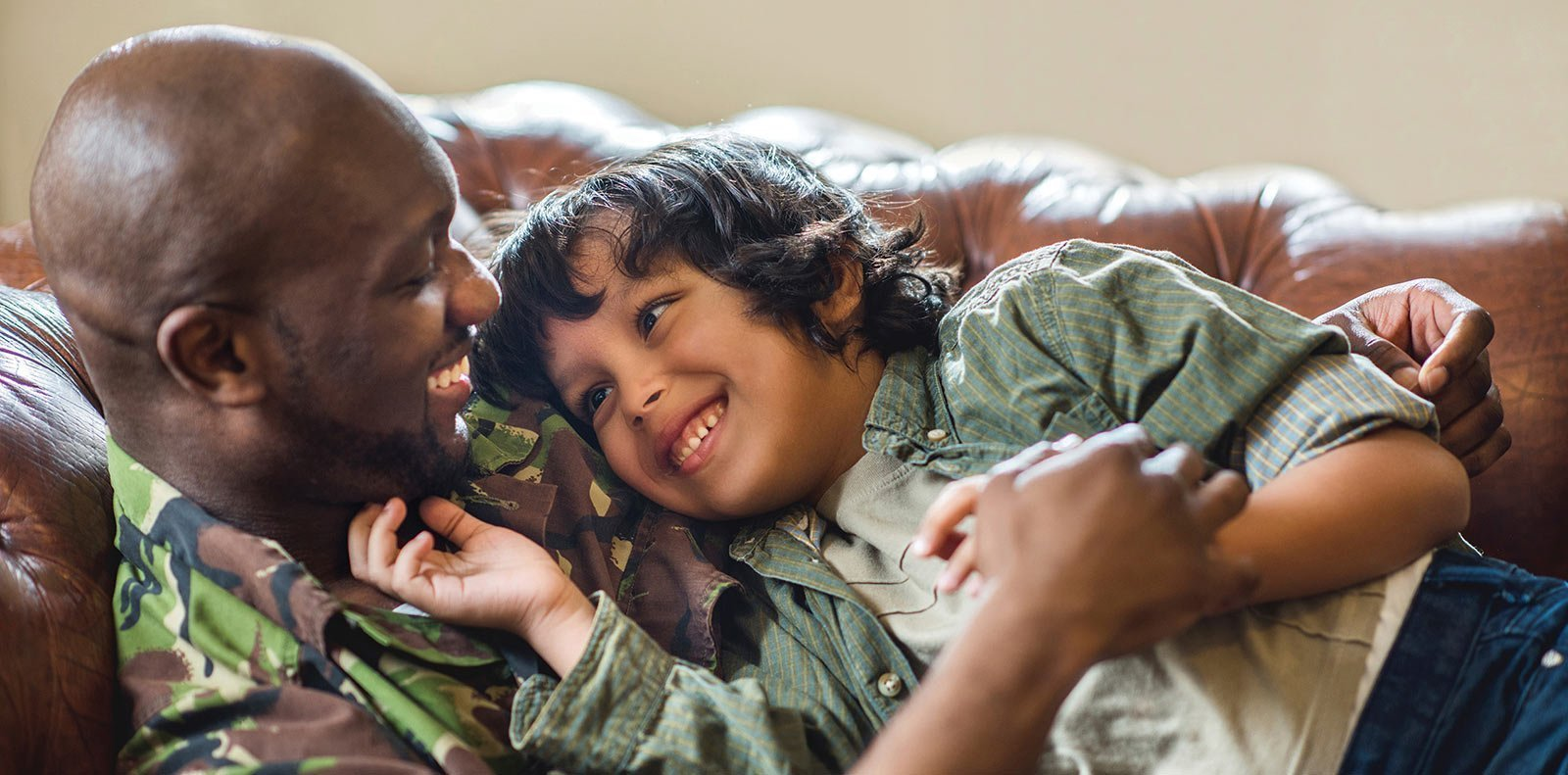military veteran father & son embrace, smiling on a leather couch