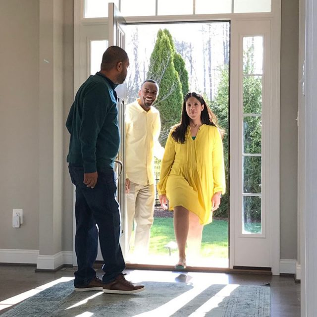Picture of a man greeting a couple as they enter the home