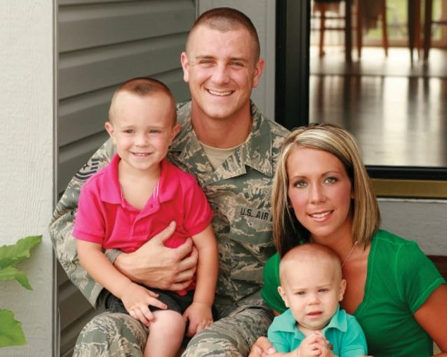 Portrait of a man wearing an Air Force uniform holding his young son alongside his wife and baby