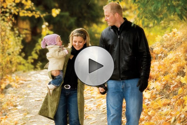 Picture of a young couple and baby walking surrounded by autumn colors